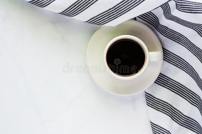 Cup of coffee with saucer and napery on white marble background. For drinks and beverage concept stock images