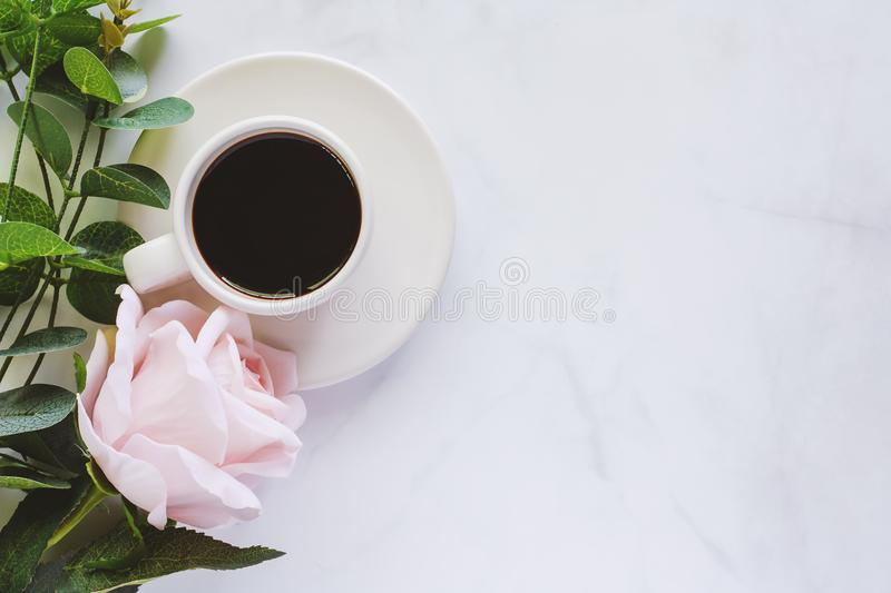 Cup of coffee with saucer and sweet pink rose on white marble ba stock photography