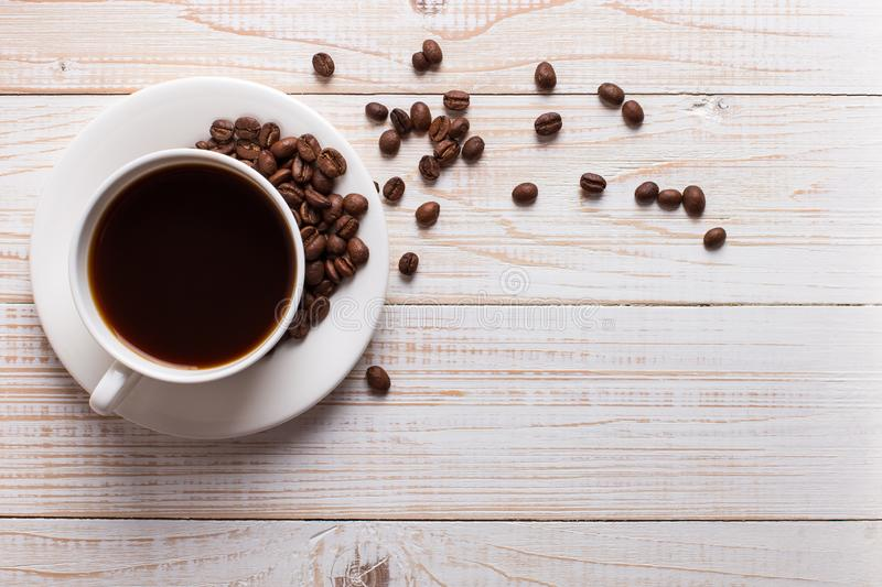 Cup of coffee with scattered coffee beans on a wooden table background. Autumn morning mood, copy space royalty free stock images