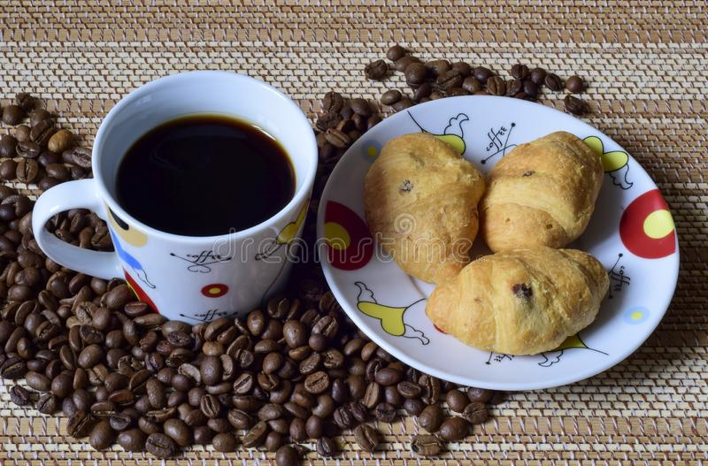 A Cup of coffee is on the scattered coffee beans, next saucer with croissants. royalty free stock image