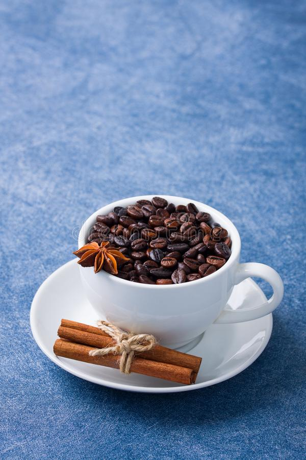 Cup of coffee seeds cinnamon anis close up. Cup of coffee with seeds, cinnamon and anis on blue background. Vertical orientation, place for copy space, close up stock image
