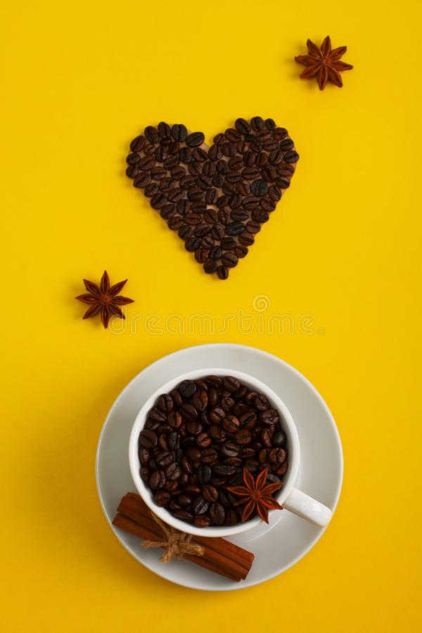 Cup of coffee seeds cinnamon anis coffee heart. Cup of coffee seeds, cinnamon, anis and coffee heart shape on yellow background. I love coffee, coffee love royalty free stock photography