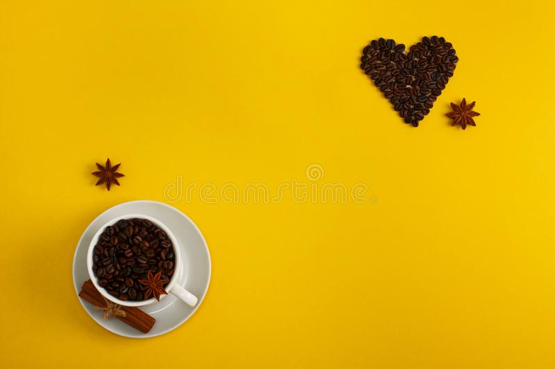 Cup of coffee seeds cinnamon anis coffee heart. Cup of coffee seeds, cinnamon, anis and coffee heart shape on yellow background, close up. I love coffee, coffee stock photography
