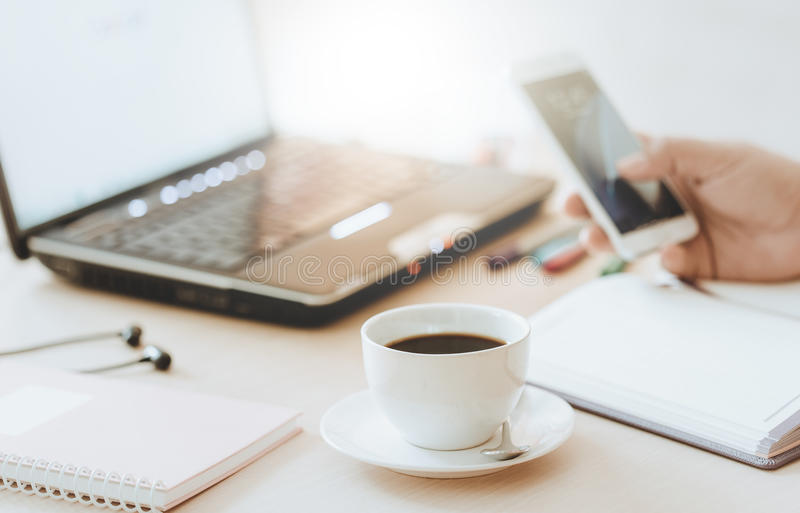 Cup of coffee and smart phone with hand of business man using laptop computer. stock photo