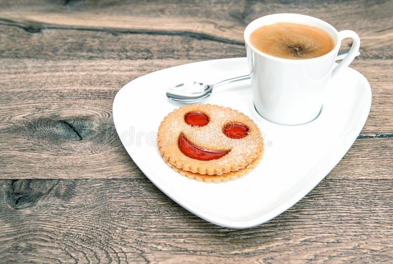 Cup coffee smiley face cookie. Funny breakfast stock photo
