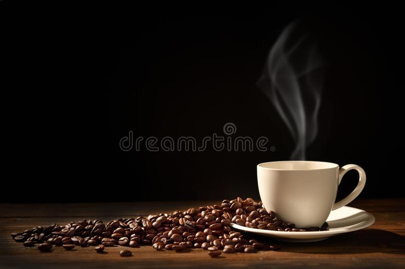 Cup of coffee with smoke and coffee beans stock photo
