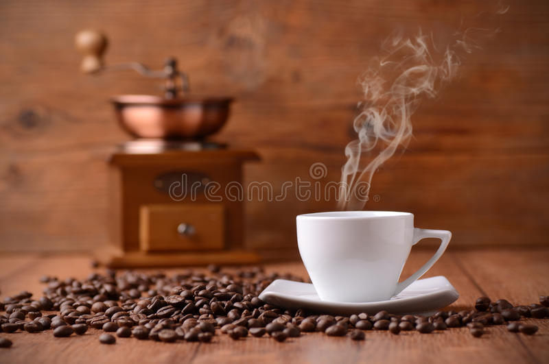 Cup of coffee. With smoke and the grinder in the background royalty free stock images