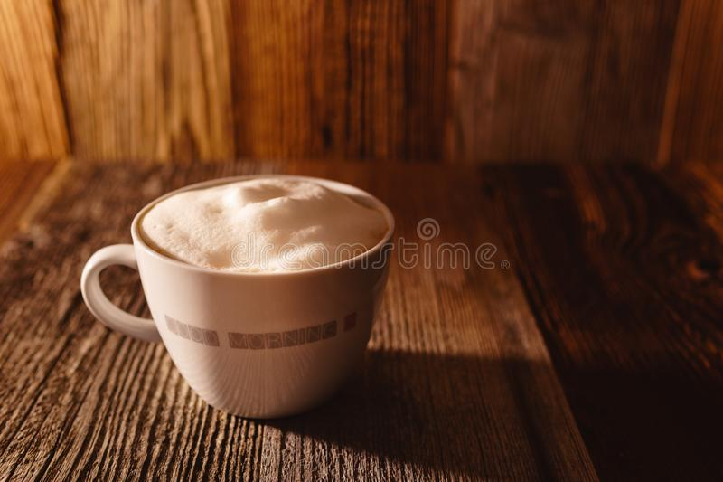 Cup of coffee with soy milk foam on wooden table in moody morning light - angled royalty free stock photos