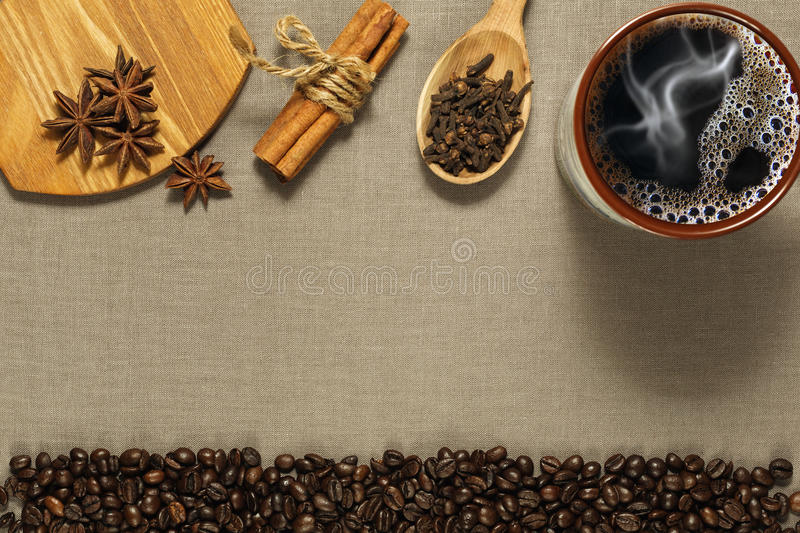 Cup of coffee, spices and roasted coffee beans on the rude textile background stock images