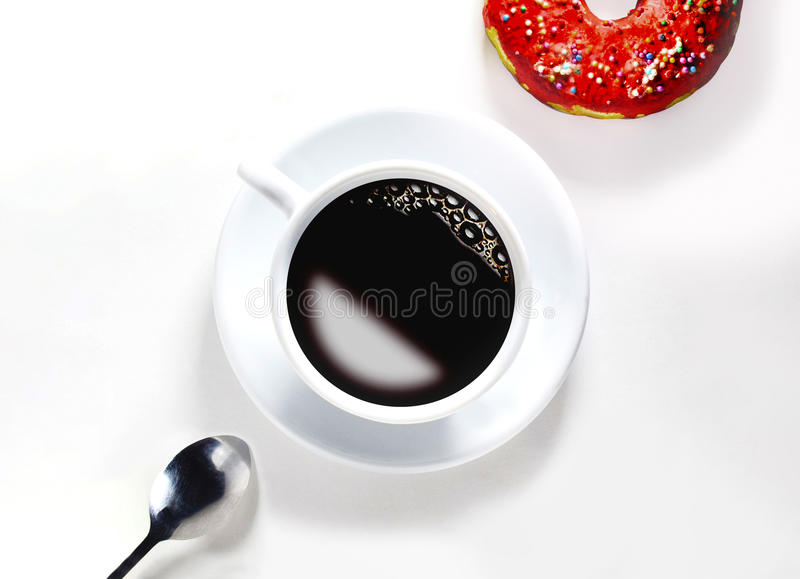 A cup of coffee with a spoon and a donut stock photo