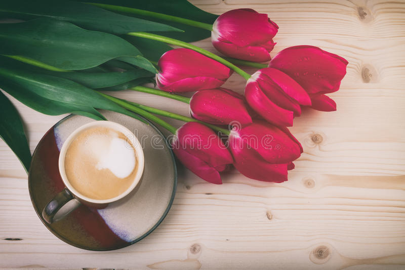 Cup of coffee with spring flowers red tulips on wooden table Vintage style stock photo