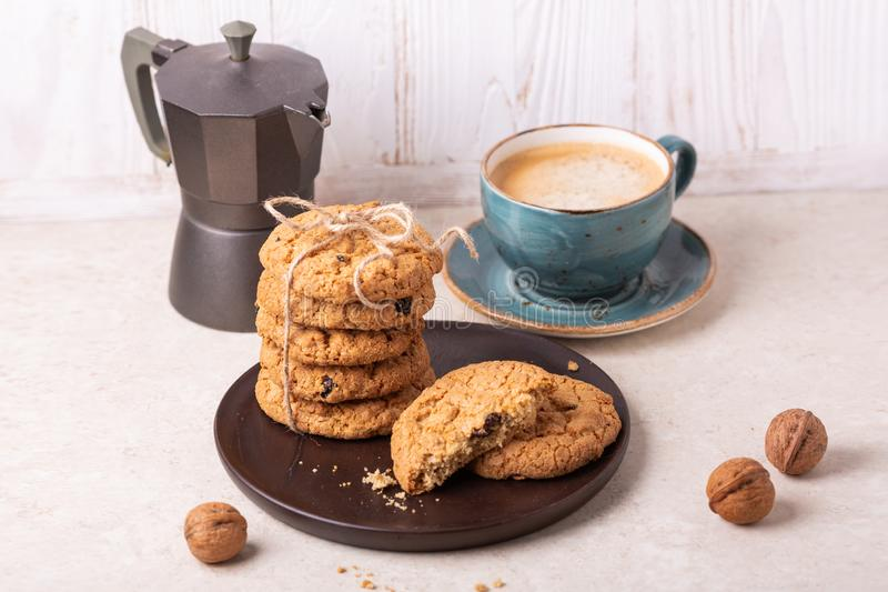 Cup of coffee, stack of oatmeal cookies, coffee maker on white wooden background Homemade bakery royalty free stock photo