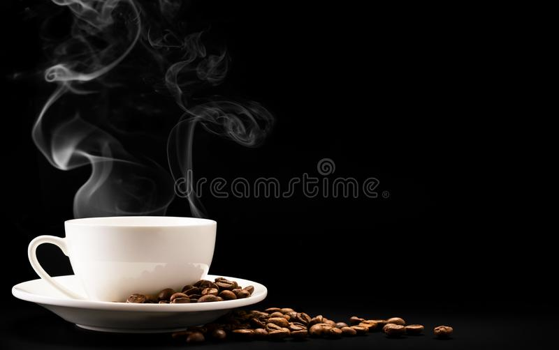 Cup coffee with steam and beans on a black background, a place for text. A Cup of hot coffee with steam and beans on a black background, a place for text stock photography