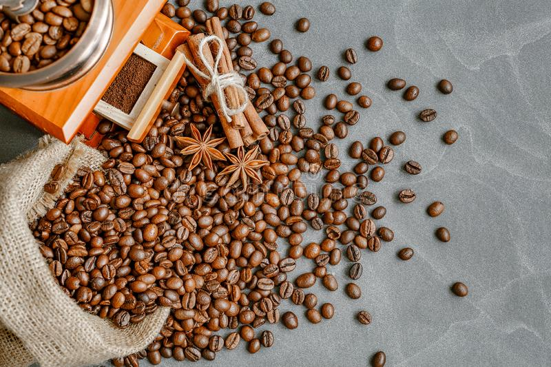 Cup of coffee with steam, coffee beans, chocolate pieces, cinnamon sticks, white and brown sugar, and scoop on burlap background. stock photography