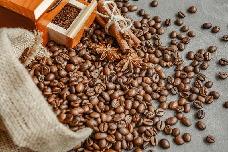 Cup of coffee with steam, coffee beans, chocolate pieces, cinnamon sticks, white and brown sugar, and scoop on burlap background. stock photo