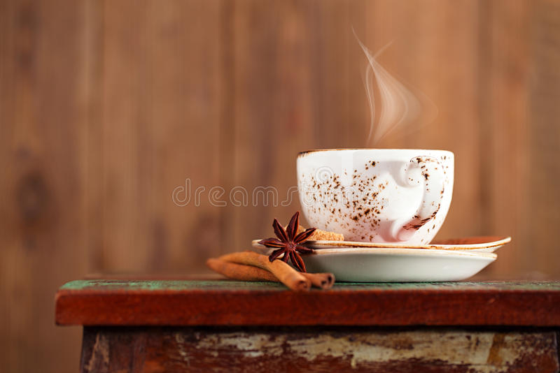 Cup of coffee with steam, cinnamon, anise on a beautiful rustic. Background royalty free stock photography