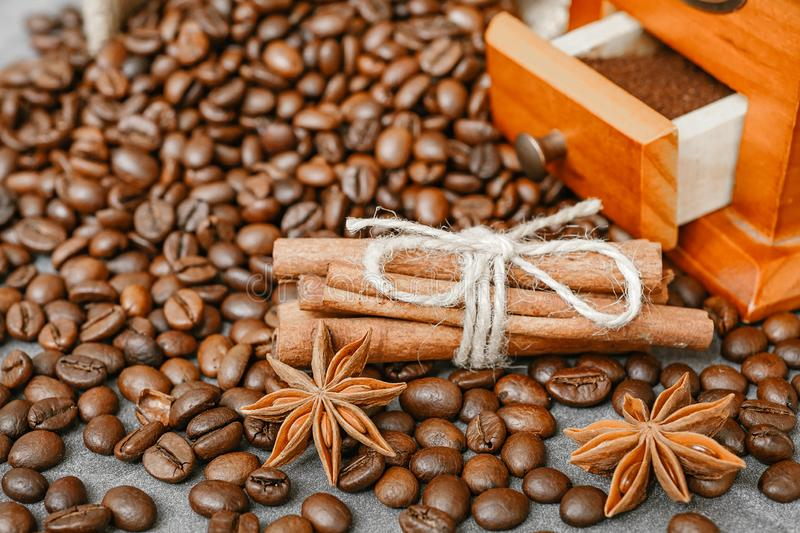 Cup of coffee with steam, coffee beans, chocolate pieces, cinnamon sticks, white and brown sugar, and scoop on burlap background. royalty free stock image