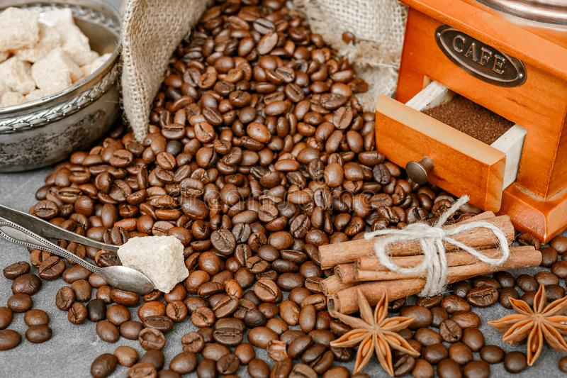 Cup of coffee with steam, coffee beans, chocolate pieces, cinnamon sticks, white and brown sugar, and scoop on burlap background. stock photos