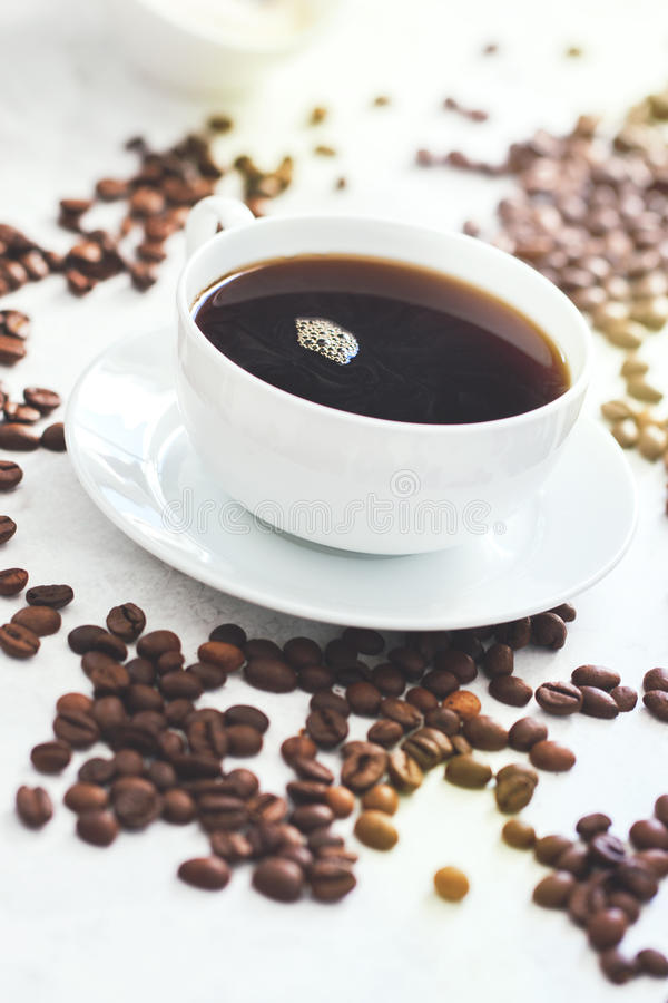 Cup of coffee with steam and coffee beans. Closeup, selective focus royalty free stock image