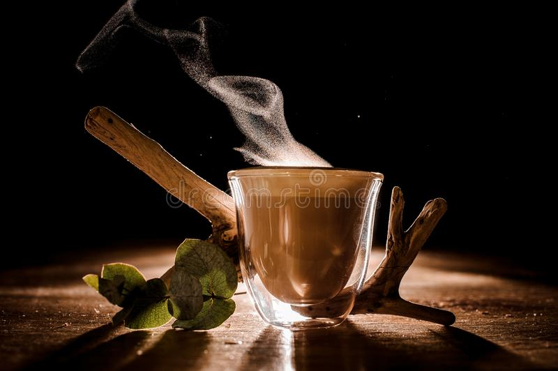 Cup of coffee with steam from it. Near plant decor located on the wooden table stock photos