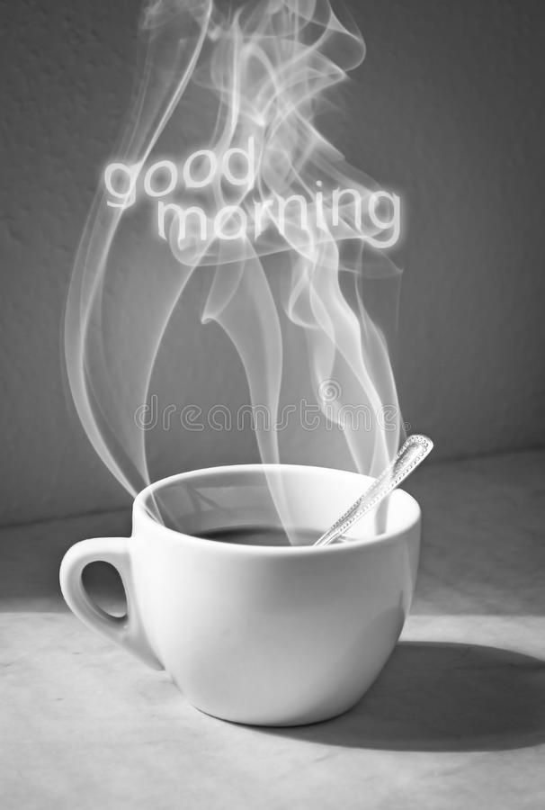 Cup of coffee with steam and good morning text. On the table royalty free stock images