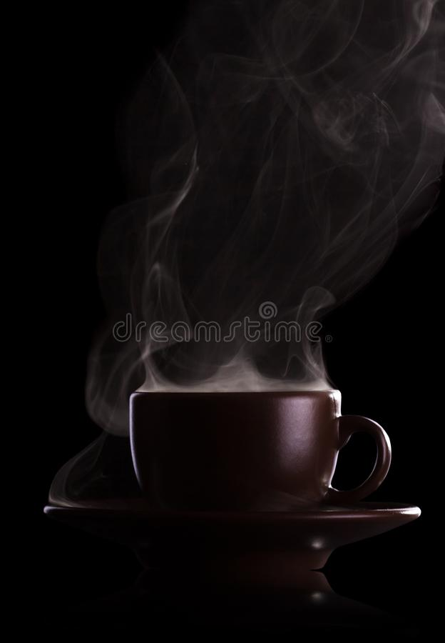 Cup of coffee with steam on black. Cup of fragrant hot coffee with steam on black background stock images