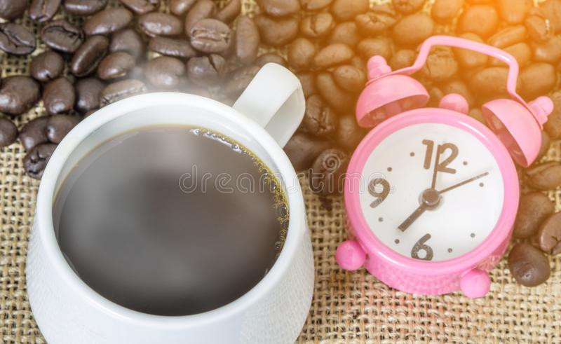 Cup of coffee with steam and pink clock. On table with coffee beans background. Concept coffee and time stock photography