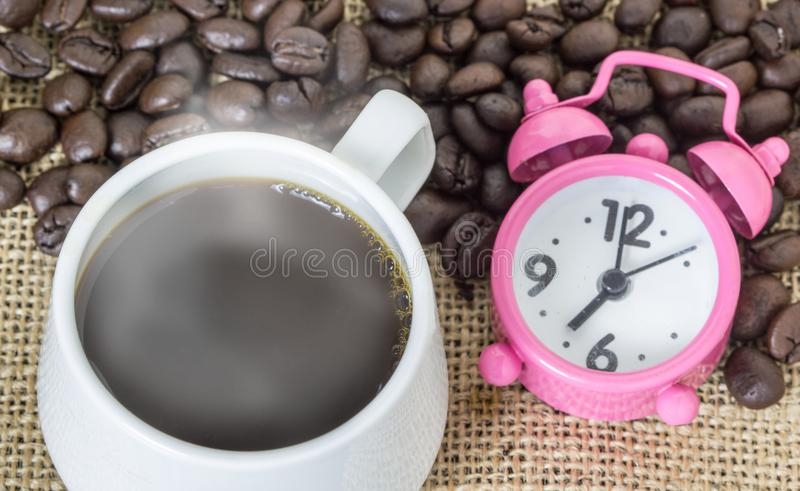 Cup of coffee with steam and pink clock on table with coffee beans background. Concept coffee and time.  royalty free stock photo