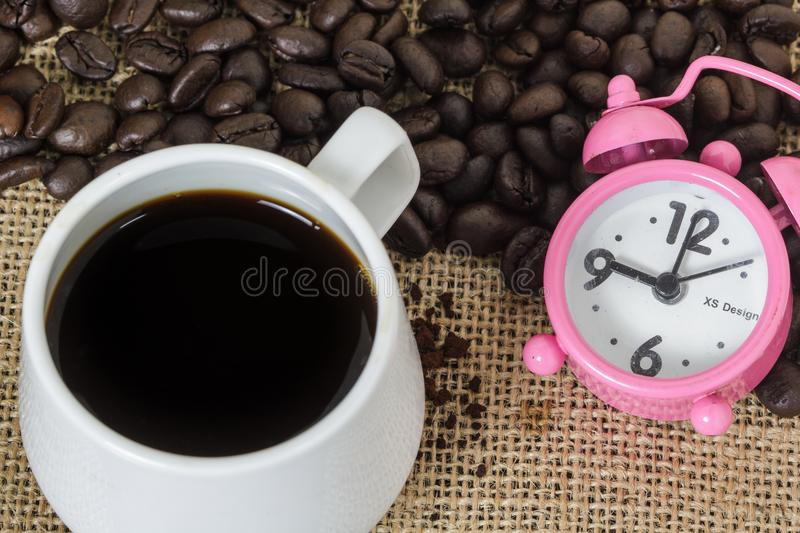 Cup of coffee with steam and pink clock on table with coffee beans background. Concept coffee and time. Cup of coffee with steam and pink clock on table with royalty free stock photo