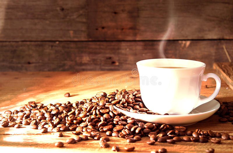 Cup of coffee with steam, roasted coffee beans. On old wooden table. Copy space. Tinted toned image royalty free stock photos