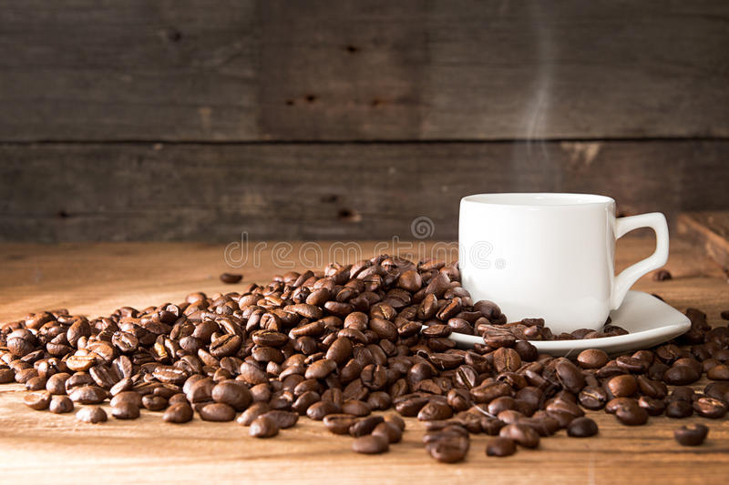 Cup of coffee with steam, roasted coffee beans. Over on old wooden table. Copy space stock image