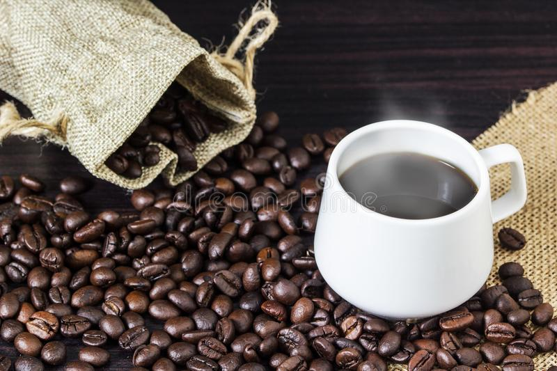 Cup of coffee with steam on table with coffee beans background.  stock image