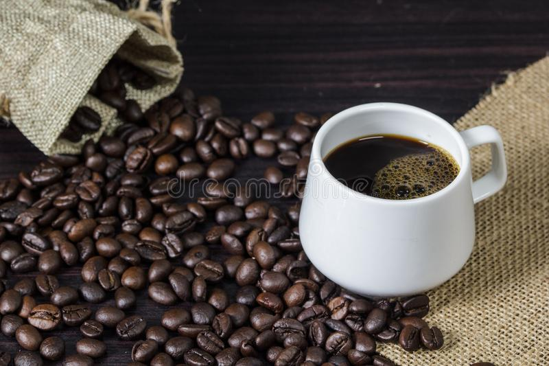 Cup of coffee with steam on table with coffee beans background. Cup of coffee with steam on table with coffee beans background royalty free stock photography