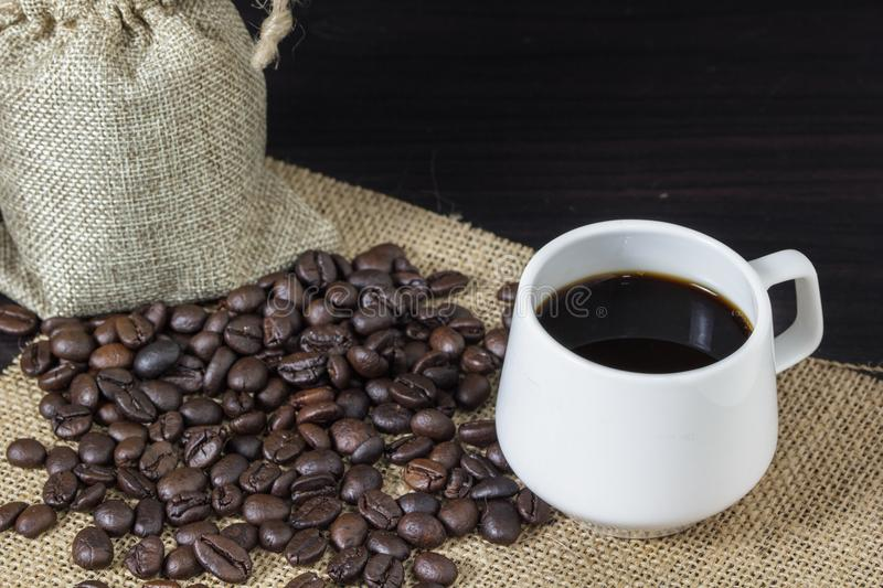 Cup of coffee with steam on table with coffee beans background. Cup of coffee with steam on table with coffee beans background stock photography