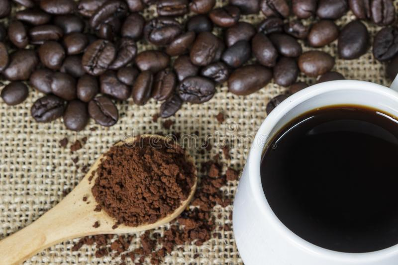 Cup of coffee with steam on table with coffee beans background. Cup of coffee with steam on table with coffee beans background royalty free stock images