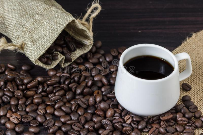 Cup of coffee with steam on table with coffee beans background. Cup of coffee with steam on table with coffee beans background royalty free stock photo
