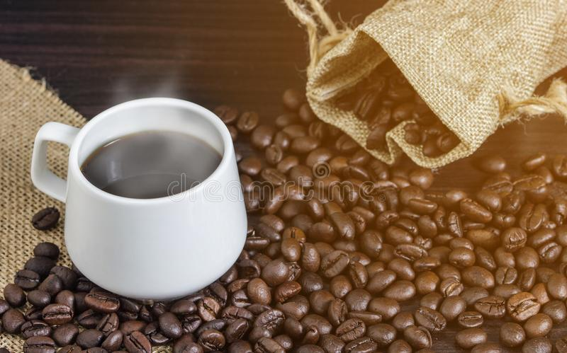 Cup of coffee and steam on table with coffee beans background.  stock images