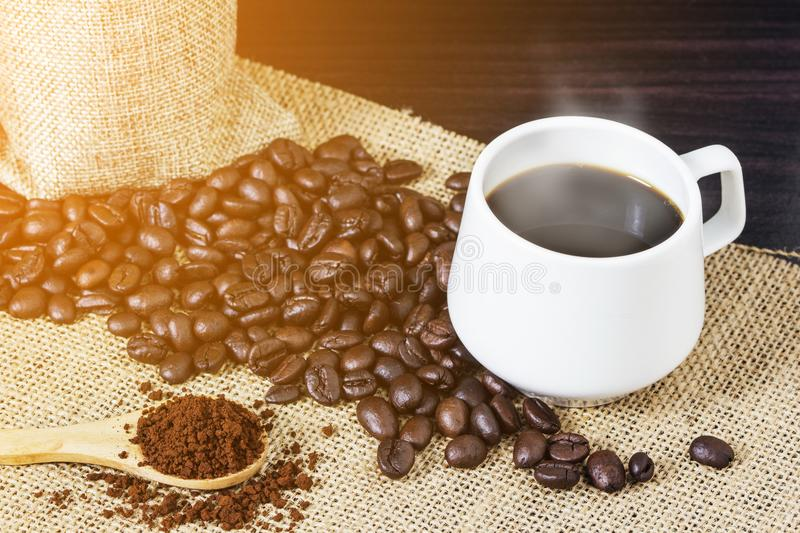 Cup of coffee with steam on table with coffee beans background.  stock photography
