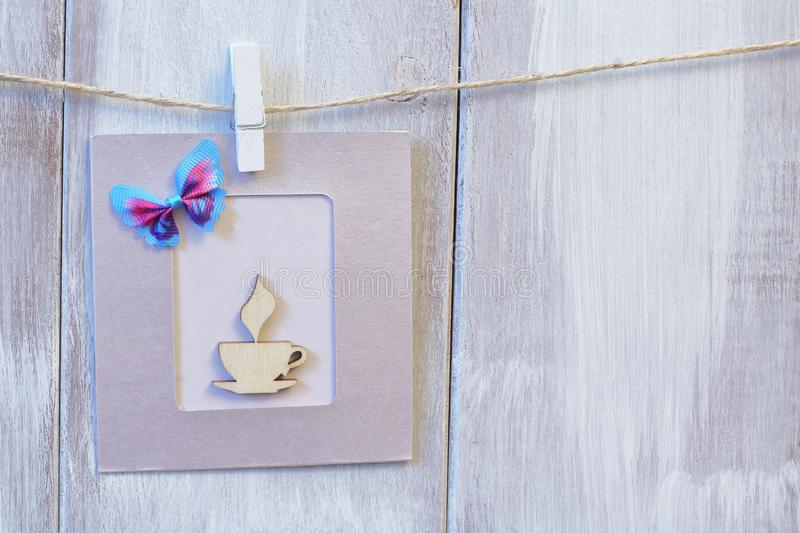 Card of gentle lilac color with stylized wooden cup of coffee and decorative butterfly on light wooden background royalty free stock photo