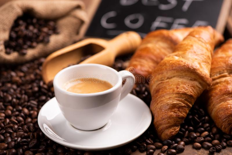 Cup of coffee surrounded by coffee beans royalty free stock photo
