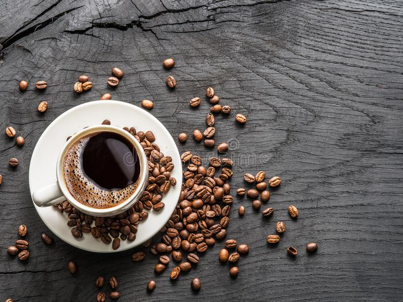 Cup of coffee surrounded by coffee beans. Top view. stock photos