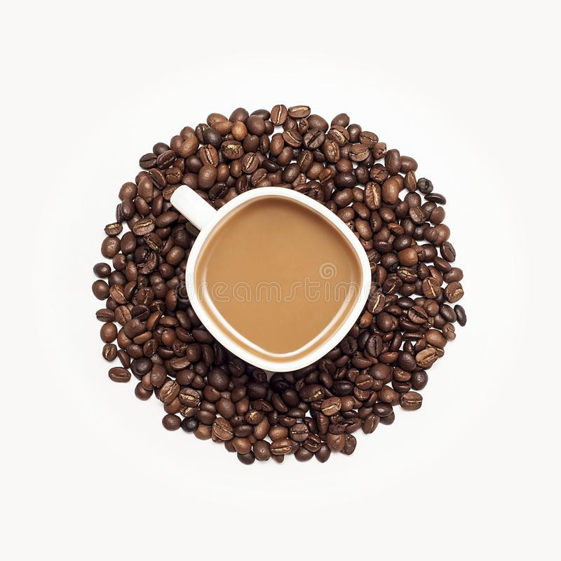 Cup of coffee surrounded by coffee beans royalty free stock image