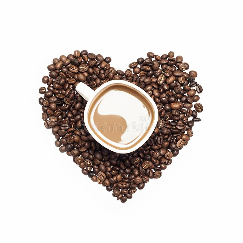 Cup of coffee surrounded by coffee beans in shape of heart stock photo
