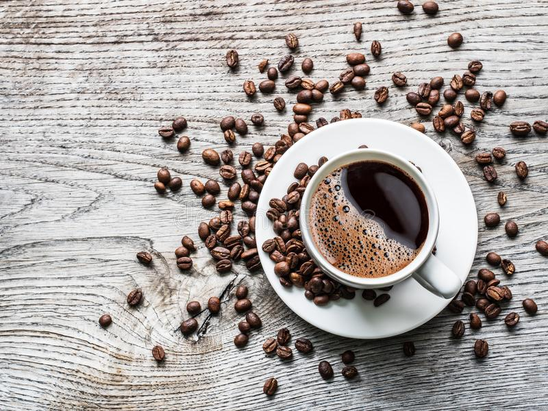 Cup of coffee surrounded by coffee beans. Top view. stock image