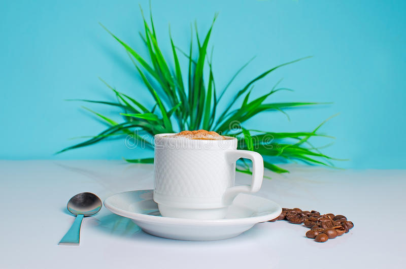 Cup of coffee on the table with beans on a blue background royalty free stock photos