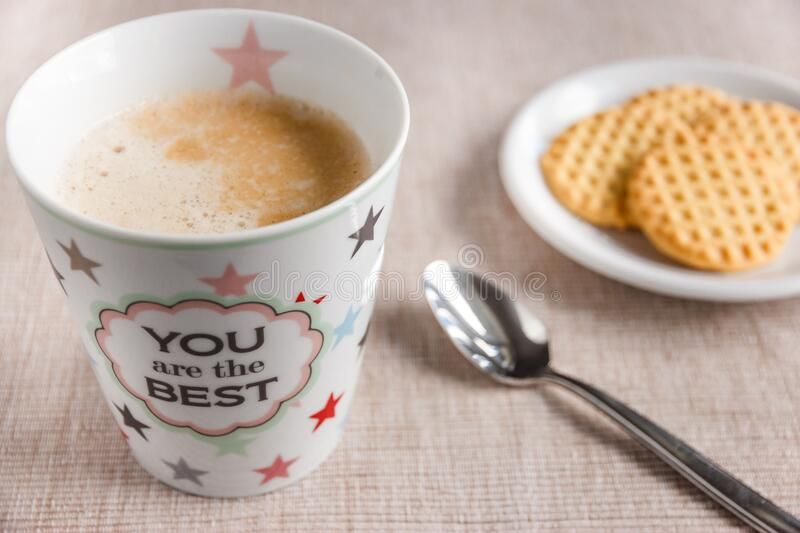 Cup of coffee on table with biscuits stock images
