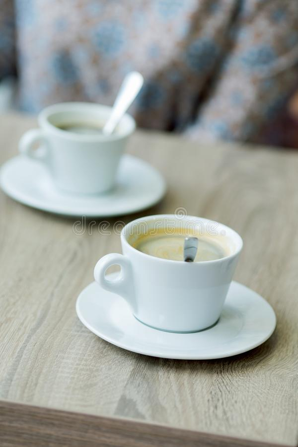 Cup of coffee on a table in a cafe close-up. With shallow depth of field stock photography