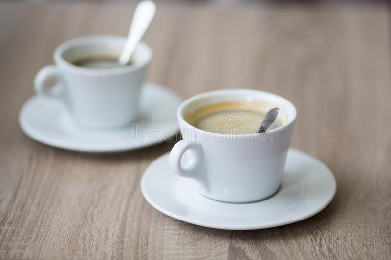 Cup of coffee on a table in a cafe close-up. With shallow depth of field stock photos