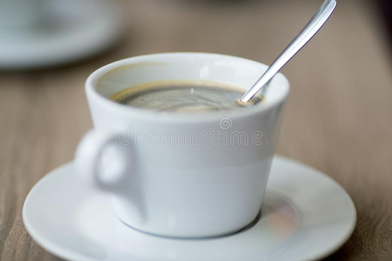 Cup of coffee on a table in a cafe close-upwith shallow depth o. Cup of coffee on a table in a cafe close-up with shallow depth of field royalty free stock photography