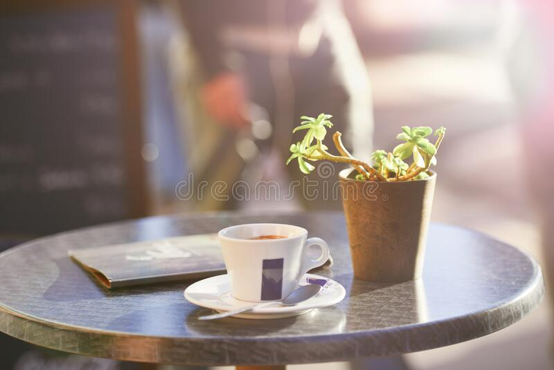 Cup of coffee on table beside plant stock photos